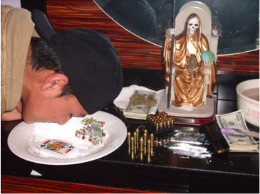 Mexican Gang Member Snorting Cocaine (ala Scarface) Next to Bullets, Money, and Santa Muerte Statue. Gang Social Media—October 2010